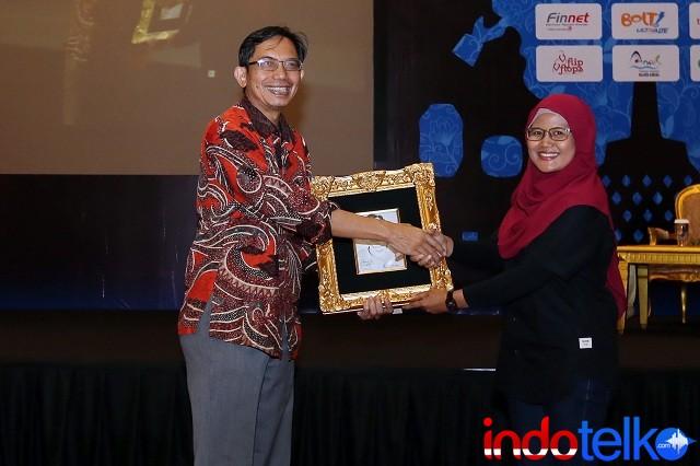 Pemberian cinderamata dari Direktur Marketing IndoTelko Group Ibu Bungsu Parlinasari kepada Ketua Asosiasi Prakarsa Indonesia Cerdas Bapak Suhono Harso Supangkat