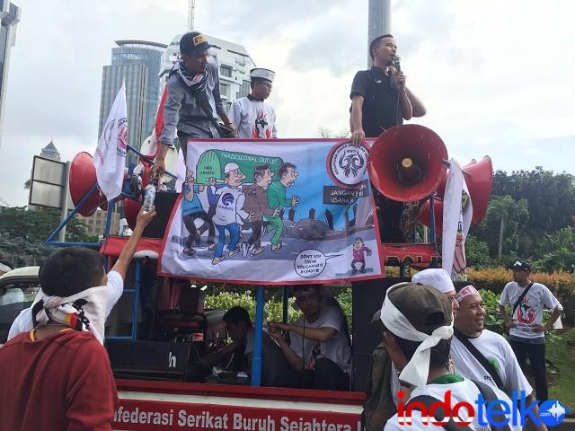Orator dari peserta aksi berteriak tentang suara dari pemilik outlet yang tak didengar oleh Menkominfo Rudiantara terkait registrasi kartu keempat.